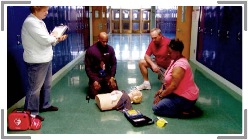 teachers in school hallway during CPR training video