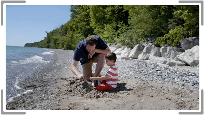 Father and son on the beach building sandcastle