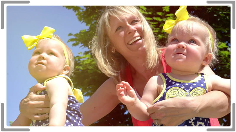 Woman with twin babies looking happy for social media video