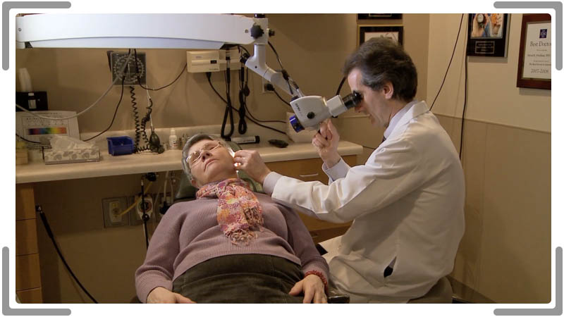 audio doctor looking in patents ear with machine in a medical video
