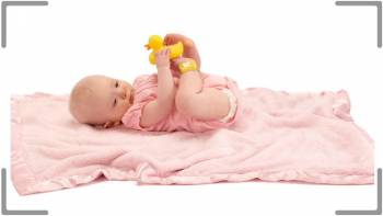 Baby laying on blanket playing with duck