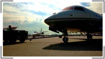 corporate jet being towed out of a hanger