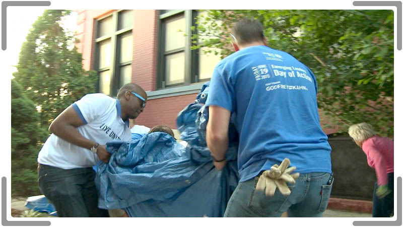 two men folding a tarp cleaning up the community in socail media video