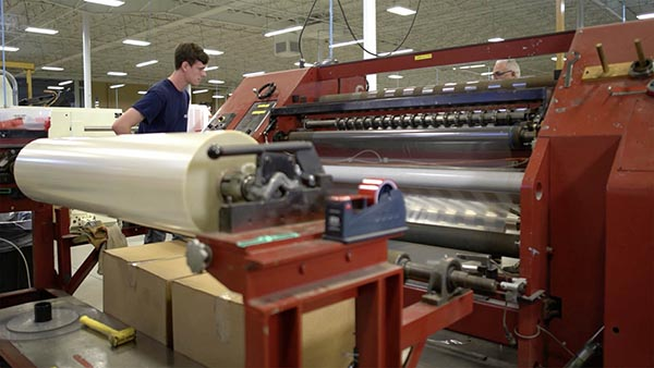 man at machine in manufacturing plant