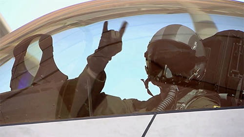 pilot in fighter jet giving hang loose hand single