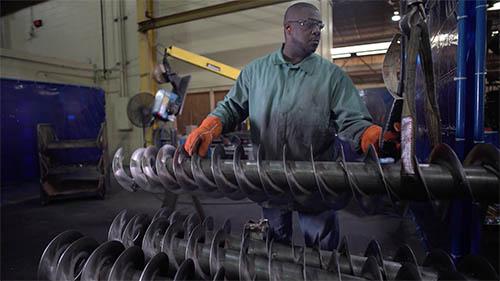 Man in manufacturing plant asalbleming screw conveyor